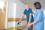 Asian female doctor reassuring mature elderly man with walker. Man and woman smiling happy in the hospital aisle. Retirement community concept - 260312735