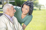 Asian female doctor playing and smiling with mature elderly man in the hospital garden - 260312737