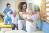 Couple of nurses helping active senior couple at rehab gym. Retirement community concept - 260313199