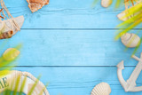 Summer sea travel background. Shells, belt and anchor on blue wooden table. Space for text in the middle. - 260323159