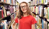 education, school and people concept - smiling teenage student girl in glasses and red t-shirt over book shelves in library background