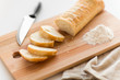 canvas print picture - food, junk-food and unhealthy eating concept - close up of white ciabatta bread on wooden cutting board, knife and kitchen towel