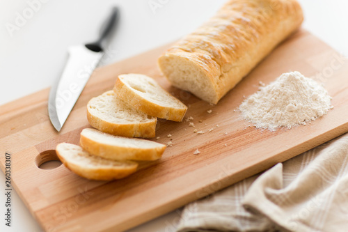 canvas print picture food, junk-food and unhealthy eating concept - close up of white ciabatta bread on wooden cutting board, knife and kitchen towel