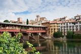 colorful houses  along river Brenta in Bassano del Grappa, Italy. With reflection in water and old wooden bridge