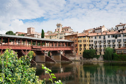colorful houses  along river Brenta in Bassano del Grappa, Italy. With reflection in water and old wooden bridge - 260339753