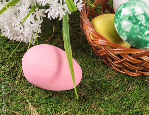 canvas print picture Wooden basket with Easter eggs and flowers on the grass field.