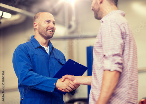 auto service, repair, maintenance, gesture and people concept - mechanic with clipboard and man or owner shaking hands at car shop © Syda Productions