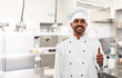 cooking, profession and people concept - happy male indian chef in toque showing thumbs up over restaurant kitchen background - 260343728