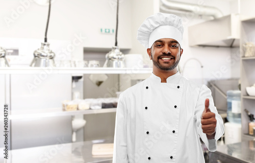 cooking, profession and people concept - happy male indian chef in toque showing thumbs up over restaurant kitchen background © Syda Productions