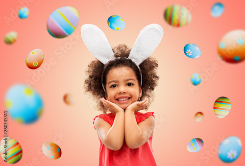 easter, holidays and childhood concept - happy little african american girl wearing bunny ears headband posing over living coral background and colored eggs © Syda Productions