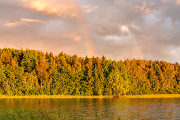 Rainbow over the lake and forest at sunset on a summer day