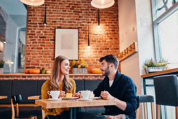 Picture of young couple at cafe. Young woman and man at coffee shop.