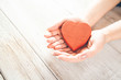 woman hand red heart on the wooden desk