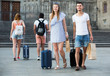 Positive couple in shorts with luggage