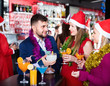 Man and two women with cocktails in Santa hats celebrating at nightclub