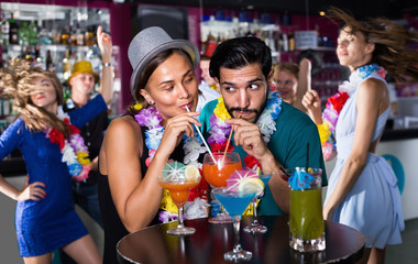 Man with woman in lei are drinking cocktails on party