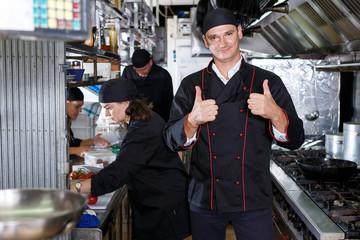 Cheerful cooks at restaurant kitchen