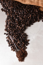 "Постер, картина, фотообои ""High angle view of a burlap bag of roasted coffee beans spilling onto the surface with a spoonful of coffee grounds"""