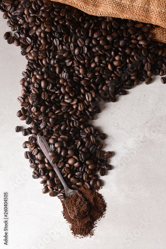 High angle view of a burlap bag of roasted coffee beans spilling onto the surface with a spoonful of coffee grounds