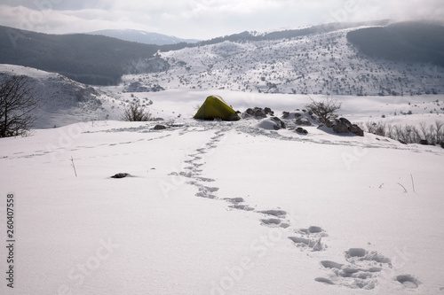 Boot Traces In The Snow Lead To A Tent Agaist Winter Landscape