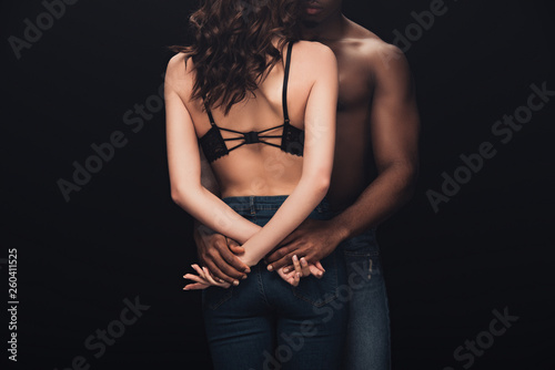 back view of african american man holding hands with sexy woman isolated on black