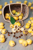 The vertical photo of a basket with chinese fruit, loquat, over wooden background