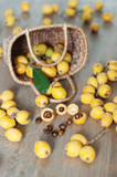 The above view of the basket with loquat, asian fruit, and its seeds on the wooden background