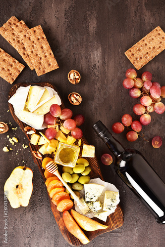 Cheese set on a plate laid out on a beige background. Different types of cheeses: Camembert, Parmesan, blue cheese, olives, honey, grapes. © ksu_ok