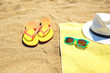 Flip flops near towel with hat and sunglasses