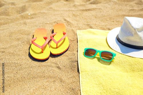 fototapeta na ścianę Flip flops near towel with hat and sunglasses