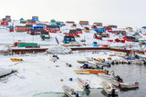 Harbor area with motorboats and colorful inuit houses in backgroung, Aasiaat city