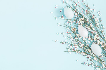 Easter composition. Easter eggs, white flowers on pastel blue background. Flat lay, top view, copy space
