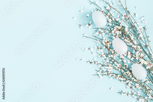 Easter composition. Easter eggs, white flowers on pastel blue background. Flat lay, top view, copy space - 260451176