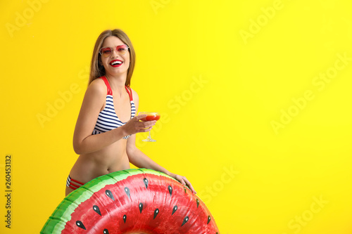 Leinwandbild Motiv Beautiful young woman with inflatable ring and cocktail on color background