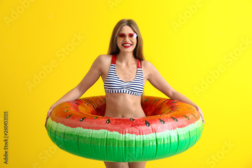 Leinwandbild Motiv Beautiful young woman with inflatable ring on color background