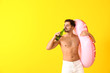 Leinwandbild Motiv Handsome man with inflatable ring and beer on color background