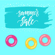 Seasonal SALE design with brush painted copy space and inflatable rings floating on a pool surface.