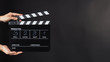 Hand is holding Black clap board or movie slate  use in video production , movie ,film, cinema industry on black background.It have write in number.