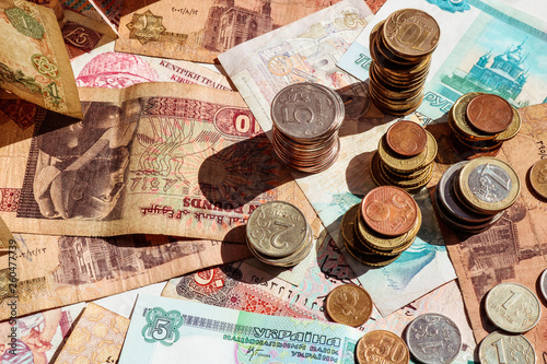 Stacks of coins on paper notes. Banknotes and coins of different countries.