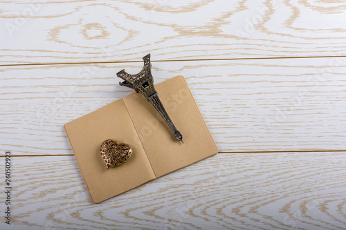 Eiffel tower miniature and a steel heart on a brown notebook on wooden background - 260502923