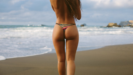 Back view of sexy woman wearing thong at the beach towards the sea. Summer vacation relax and freedom concept. Playa de Verdicio, Asturias, Spain.