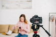 Selective focus of teenage blogger sitting in front of video camera