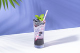 Cold and refreshing  blueberry punch cocktail with mint on purple background. summer drink