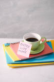 Green cup with sticker and notebooks on tabletop.