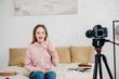 Joyful teenage blogger showing peace sign at video camera