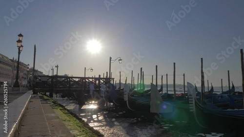 A slowmotion of covered gondolas swaying on a pier close to the paved Venice embankment. Beautiful lampposts are standing along it. The sun is shining in the middle of the blue sky