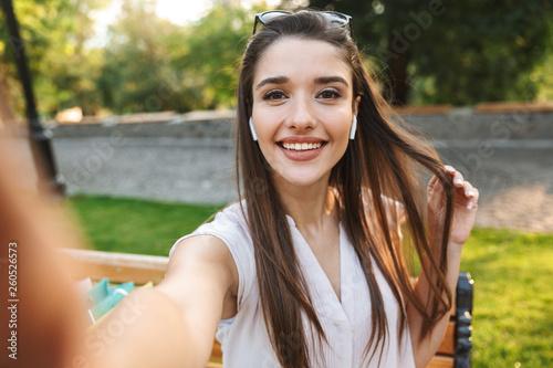 Leinwandbild Motiv Beautiful young woman taking a selfie=