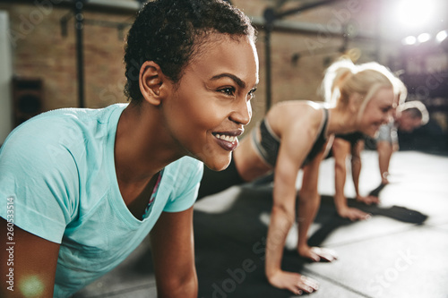 Fototapeten Fitness Smiling young woman doing pushups with others at the gym