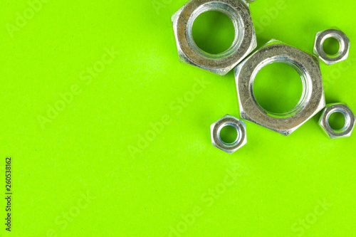 Leinwandbild Motiv Engineering tools. Bolts and nuts on green background