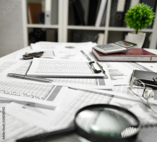 Office interior - the table with documents, reports and shelves with folder. Business financial accounting concept. © soleg